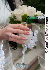 Bride holds a beautiful glass with champagne - The hand of...