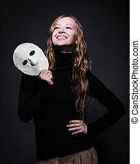 Low key portrait of a beautiful woman holding mask - Low key...