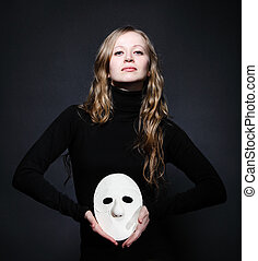 Low key portrait of a beautiful woman holding mask