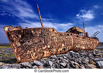 Deserted rusty ship on a rocky beach