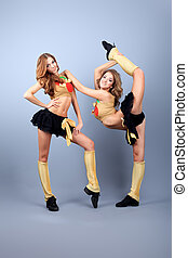 fitness flexible - Two professional cheerleaders posing at...