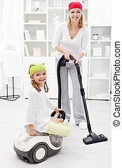 Woman and little girl cleaning the room