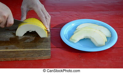 cut with knife yellow melon on red table