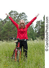 Excited woman cyclist standing on a nature with hands outstretched
