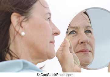 Portrait mature woman in mirror - Portrait of an attractive...