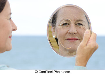 Portrait mature woman in mirror - An attractive looking...