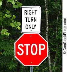 A right turn only and stop sign in front of the woods directing you on which way to go.
