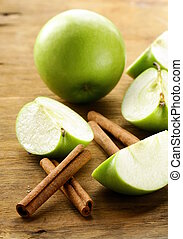 green apples and cinnamon sticks on a wooden background