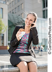 Business woman calling phone and eating
