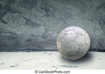 Soccer ball in an obsolete gray grunge concrete room