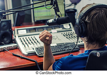 Dj working in front of a microphone on the radio, from the back