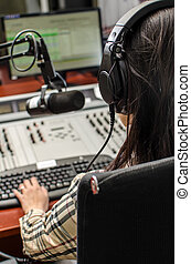 Anchorwoman sitting in front of a microphone on the radio, from the back