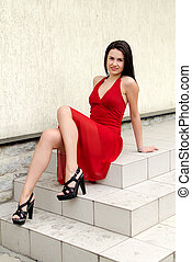 Beautiful girl in red dress posing on the stairs
