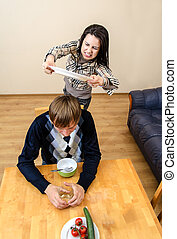Domestic violence: Wife beating her husband with a plate