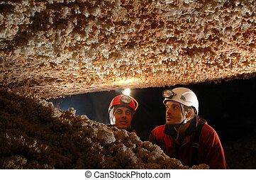 Beautiful stalactites in a cave with two speleologist...