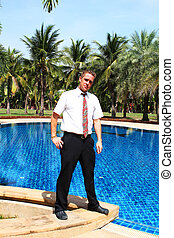 Man stood by a swimming pool.