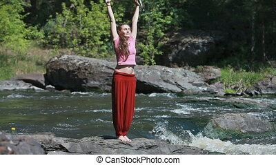 In harmony with nature - Young woman doing yoga exercises in...