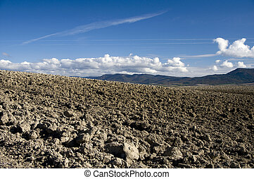 Ploughed field against blue sky