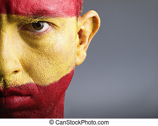 Man with his face painted with the flag of Spain