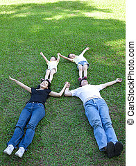 asian family lying on the grass