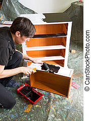 man with paintroller painter - craftsman painting a piece of...