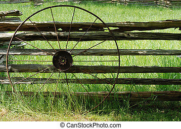 Old metal wagon wheel leaning on fence