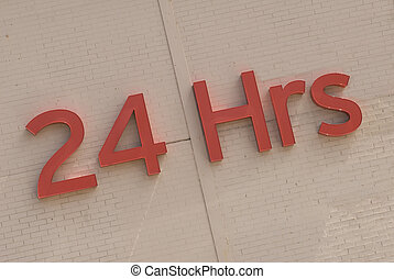 24 Hour Sign - Letters on a brick wall indicate 24 Hrs.