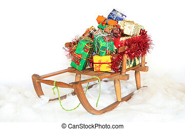 Christmas gifts - Sled in the snow with Christmas gifts on a...