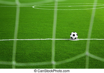 Soccer ball on green field with net foreground