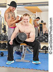 smiling young man exercising in gym