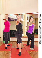 young women performing stretching - Three beautiful young...