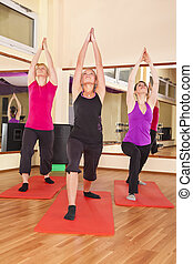three women performing stretching - Three beautiful young...