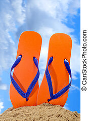 flip-flops on the beach - a pair of orange flip-flops on the...