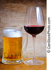 Beer mug and wine glass on a wooden background