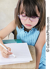 Child Sitting at School Desk With Glasses