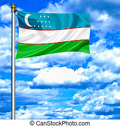 Uzbekistan waving flag against blue sky