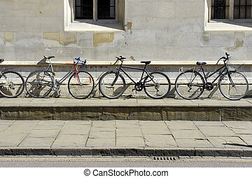 Three different types of bicycle leaning up agains an old...