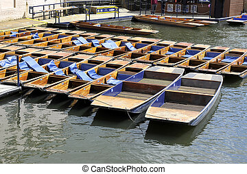 tied up wooden punts on a river in Cambridge with cushions