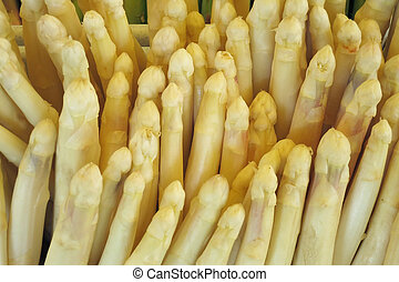 white asparagus are stangem next to each other in a market...
