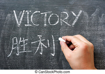 Victory - word written on a blackboard with a Chinese translation