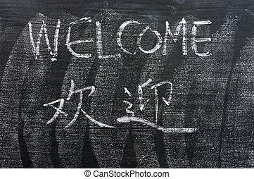 Welcome - word written on a blackboard with a Chinese version