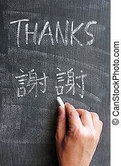Thanks - word written on a blackboard with a Chinese version