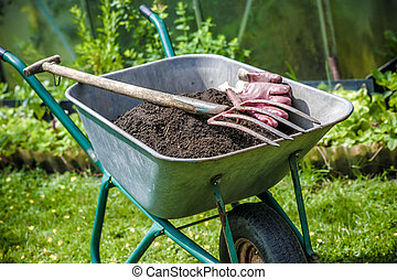 Gardening - Pitch fork and gardening gloves in wheelbarrow...