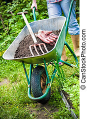 Gardening - gardener with a wheelbarrow full of humus in the...