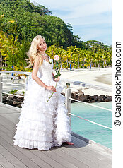 The young beautiful woman in a dress of the bride on the bridge about sea edge