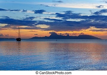 A sunset over ocean and  silhouette of boat and Orohena mountain. Polynesia. Tahiti.