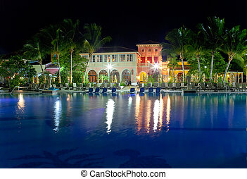Buildings with night illumination behind pool