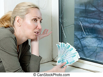 The housewife cries and counts money for repair of a double-glazed window which has burst in a frost