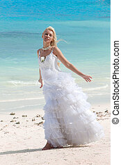 The young beautiful woman in a dress of the bride standing at sea edge