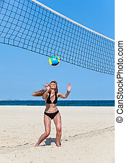 Attractive woman plays in beach volleyball